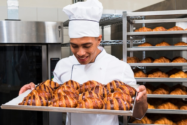 Portret uśmiechnięty młody męski piekarz patrzeje świeżego piec croissant w wypiekowej tacy