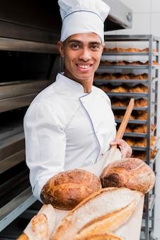 Portret uśmiechnięty młody męski piekarz pokazuje świeżo piec chleb na drewnianej łopacie