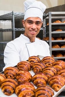 Portret uśmiechnięty młody męski piekarz trzyma świeżą croissant tacę