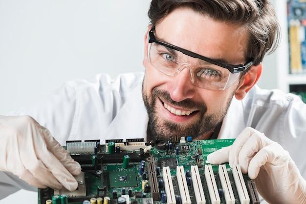 Portret uśmiechnięty młody męski technik wkłada układ scalonego w komputerowej płycie głównej