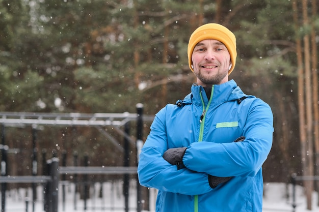 Portret uśmiechnięty młody sportowiec mężczyzna w ciepłej kurtce stojącej ze skrzyżowanymi rękami pod padającym śniegiem w obszarze treningu