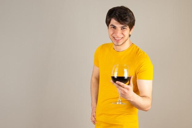 Portret uśmiechnięty model mężczyzna w żółtej koszuli stojący i trzymający kieliszek wina.