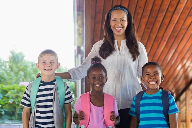 Portret uśmiechnięty nauczyciel i dzieciaki stoi wraz z ręką wokoło