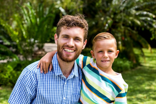 Portret uśmiechnięty ojciec i syn w jardzie