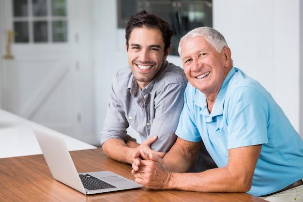 Portret uśmiechnięty ojciec i syn z laptopem