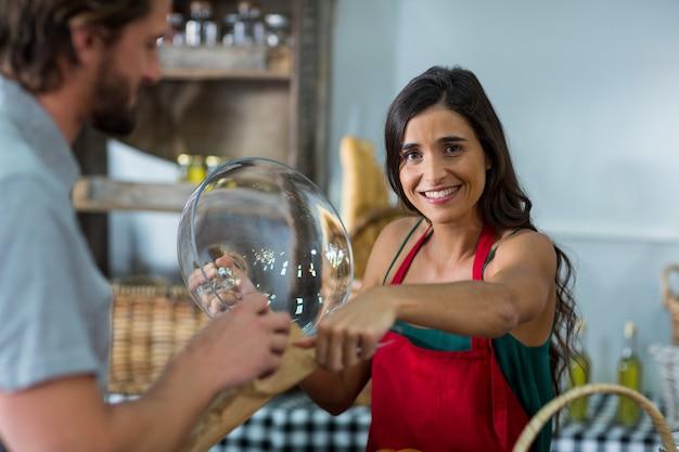 Portret uśmiechnięty personel piekarni dając paczkę klientowi płci męskiej przy kasie