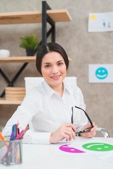 Portret uśmiechnięty piękny żeński psycholog trzyma czarnych eyeglasses w ręce