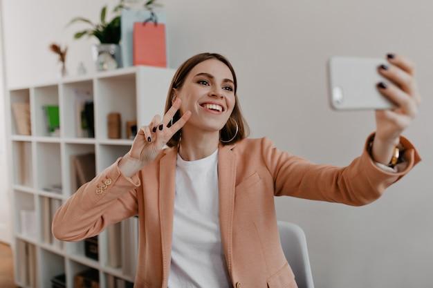 Portret uśmiechnięty pracownik biurowy z czarnym manicure w miękkiej różowej kurtce. kobieta pokazuje znak pokoju i sprawia, że selfie.
