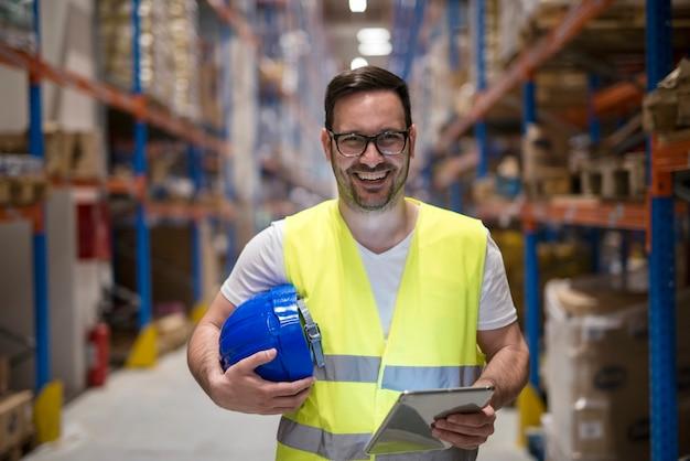 Portret uśmiechnięty pracownik magazynu z tabletu stojącego w magazynie