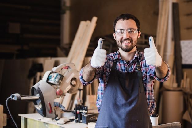 Portret uśmiechnięty pracownika budowlanego kciuk up