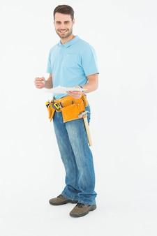 Portret uśmiechnięty pracownika budowlanego mienia clipbard nad białym tłem