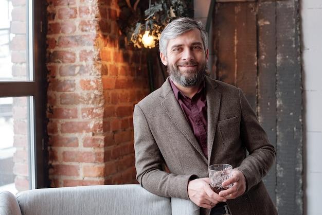 Portret uśmiechnięty przystojny biznesmen z siwą brodą, trzymając szklankę whisky w holu na poddaszu
