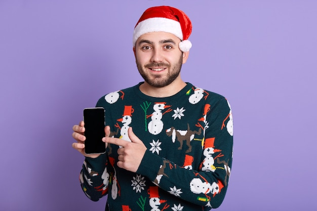 Portret uśmiechnięty przystojny brodaty mężczyzna ubiera kapelusz i zabawny sweter canta clause