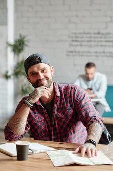 Portret uśmiechnięty przystojny młody brodaty podróżnik z tatuażami siedzi przy stole z planera i papierową mapę w kawiarni
