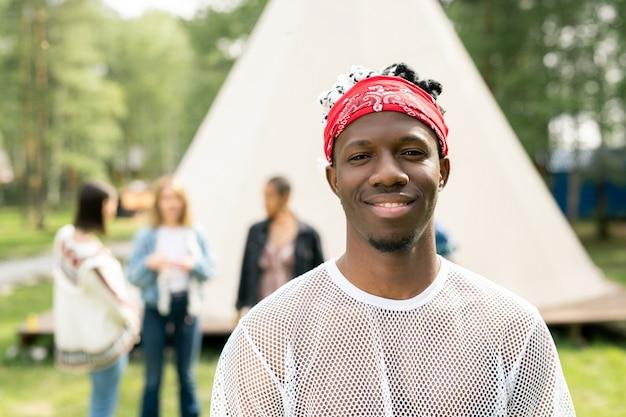 Portret uśmiechnięty przystojny młody człowiek z brodą na sobie czerwoną chustkę spędza czas na kempingu festiwalu
