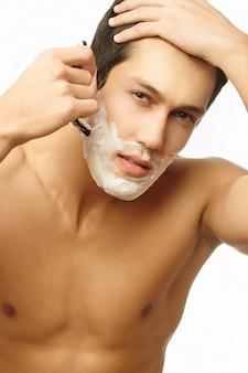 Portret uśmiechnięty przystojny pomyślny mężczyzna golenie