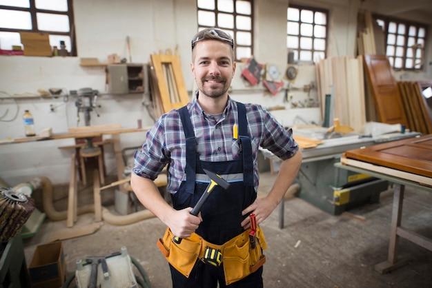 Portret uśmiechnięty przystojny rzemieślnik trzymając młotek w swoim warsztacie