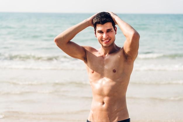 Portret uśmiechnięty przystojny seksowny mężczyzna pokazuje mięśniową dysponowaną ciało pozycję na tropikalnej plaży. wakacje lata