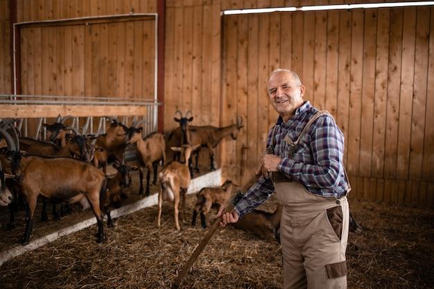 Portret uśmiechnięty rolnik lub cattleman stojący w gospodarstwie