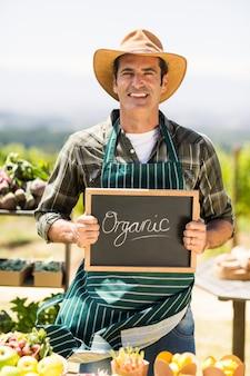 Portret uśmiechnięty rolnik trzyma organicznie znaka