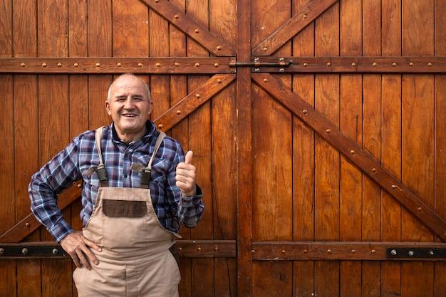 Portret uśmiechnięty rolnik, trzymając kciuki do góry i stojąc przy drewnianych drzwiach stodoły na farmie zwierząt.