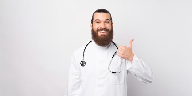 Portret uśmiechnięty rozochocony brodaty doktorski mężczyzna pokazuje kciuk up nad białym tłem