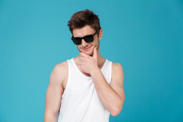 Portret uśmiechnięty rozważny mężczyzna w okularach przeciwsłonecznych