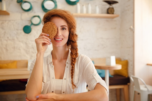 Portret uśmiechnięty rudzielec kobiety obsiadanie przy kawiarnią