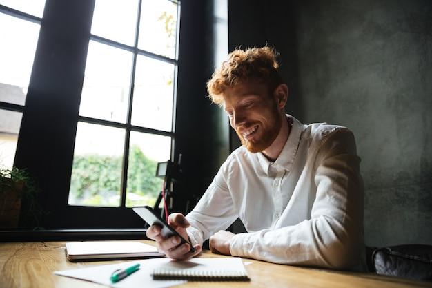 Portret uśmiechnięty rudzielec mężczyzna używa telefon komórkowego