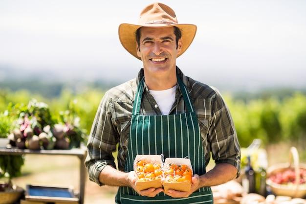 Portret uśmiechnięty średniorolny mienia pudełko owoc