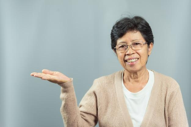 Portret uśmiechnięty stara kobieta seansu gest z ręką na szarość