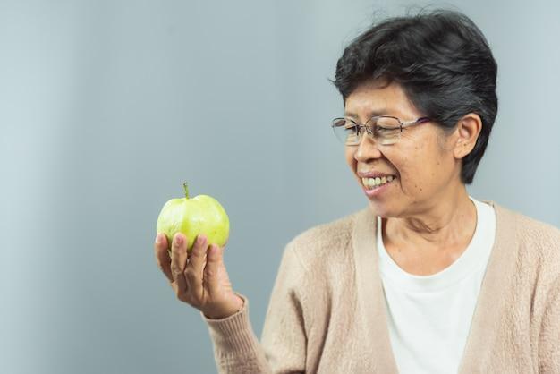 Portret uśmiechnięty starej kobiety mienia zieleni owoc na szarość