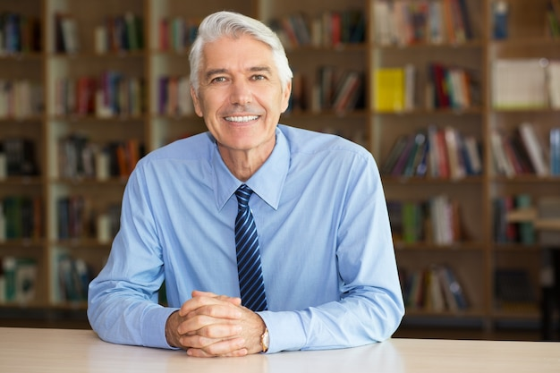 Portret uśmiechnięty starszy biznesmen na bibliotekę