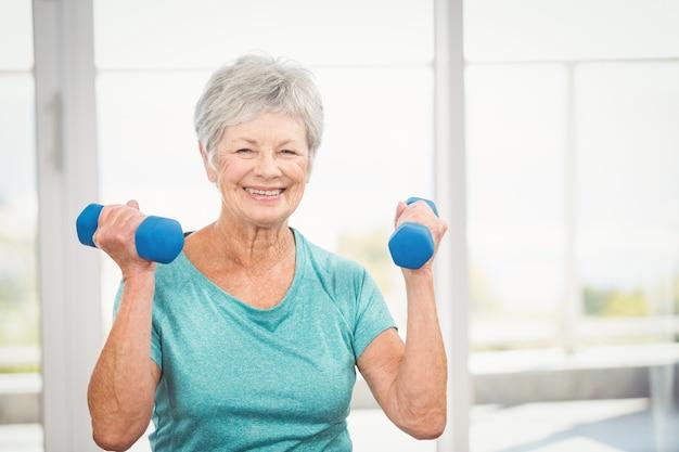 Portret uśmiechnięty starszy kobiety mienia dumbbell