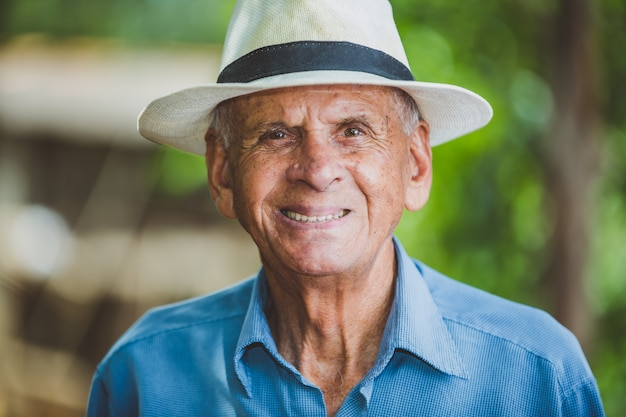Portret uśmiechnięty starszy męski rolnik z kapeluszem