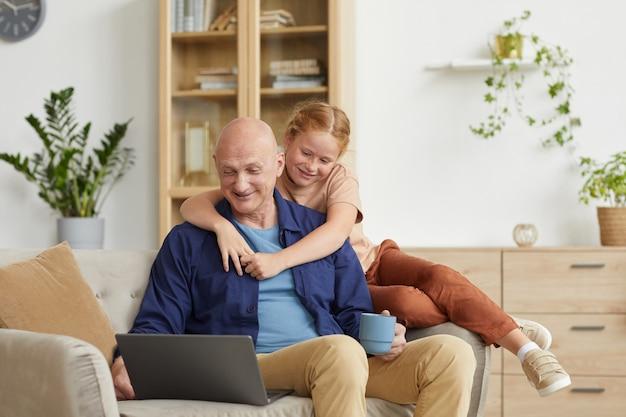 Portret uśmiechnięty starszy mężczyzna i śliczna mała dziewczynka patrząc na ekran laptopa podczas rozmowy wideo z rodziną w przytulnym wnętrzu domu
