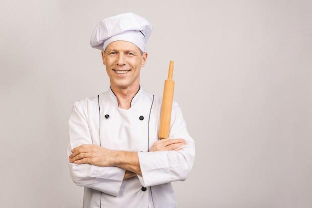 Portret uśmiechnięty starszy piekarz. pojedynczo na białej ścianie.