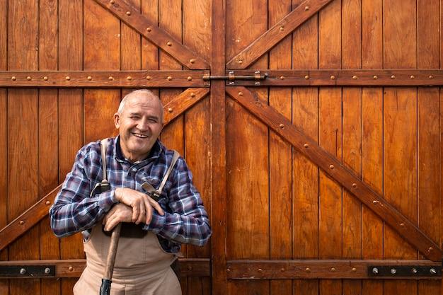 Portret uśmiechnięty starszy rolnik stojący przy drewnianych drzwiach stodoły na farmie zwierząt.