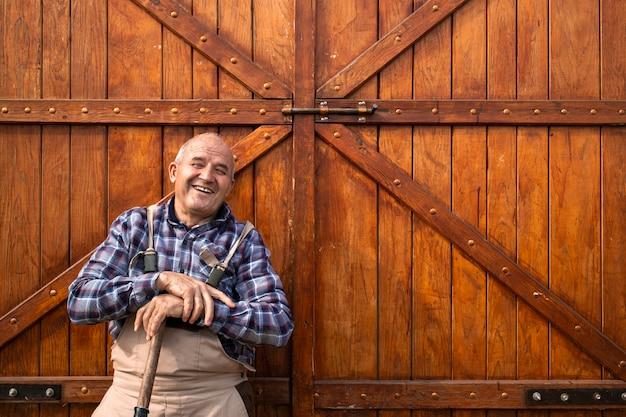 Portret uśmiechnięty starszy rolnik stojący przy drzwiach drewnianej stodoły lub spichlerza żywności na farmie zwierząt.