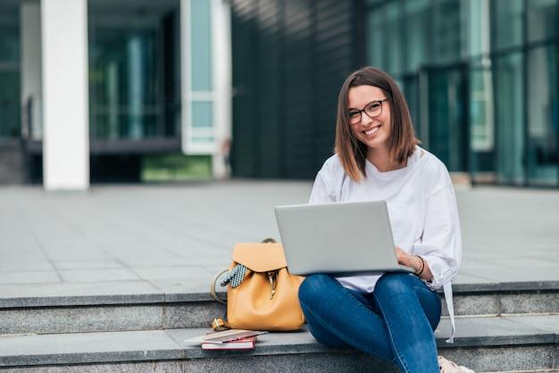 Portret uśmiechnięty studencki dziewczyny obsiadanie na schodkach w mieście i używać laptop.