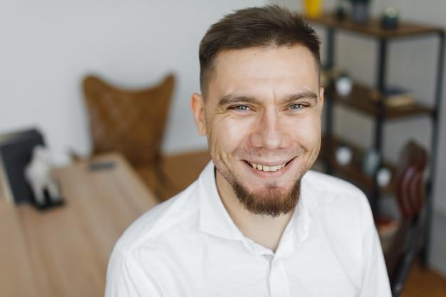 Portret uśmiechnięty szczęśliwy biznesmen w białej koszuli w biurze po ciężkim dniu pracy