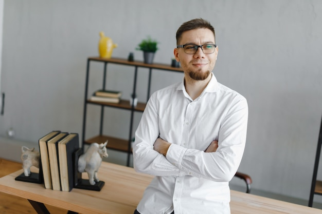 Portret uśmiechnięty szczęśliwy biznesmen w okularach i białej koszuli w biurze po ciężkim dniu pracy