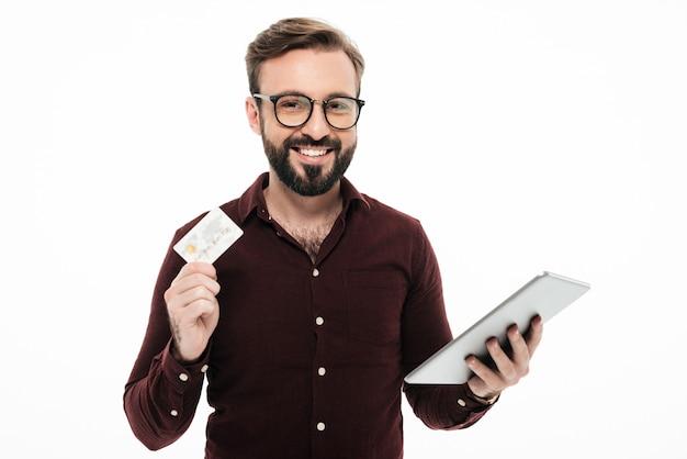 Portret uśmiechnięty szczęśliwy mężczyzna mienia pastylki komputer. zakupy internetowe