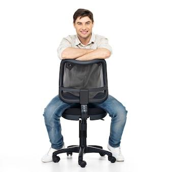 Portret uśmiechnięty szczęśliwy mężczyzna siedzi na krześle na białym tle.