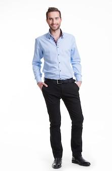 Portret uśmiechnięty szczęśliwy mężczyzna w niebieskiej koszuli i czarnych spodniach - na białym tle.