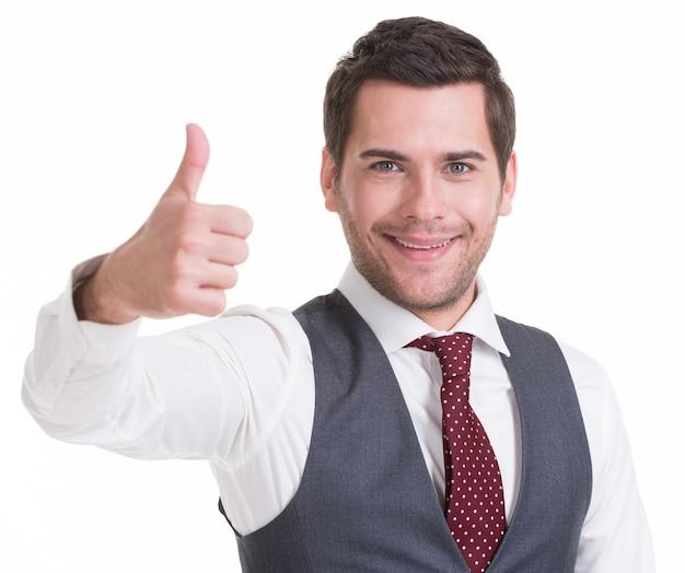 Portret uśmiechnięty szczęśliwy przystojny mężczyzna w garniturze ścianie