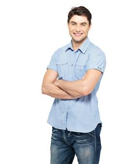 Portret uśmiechnięty szczęśliwy przystojny mężczyzna w niebieskiej koszuli na co dzień - na białym tle na białej ścianie