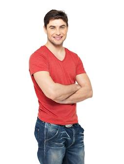 Portret uśmiechnięty szczęśliwy przystojny mężczyzna w przypadkowej czerwonej koszulce - na białym tle na białej ścianie