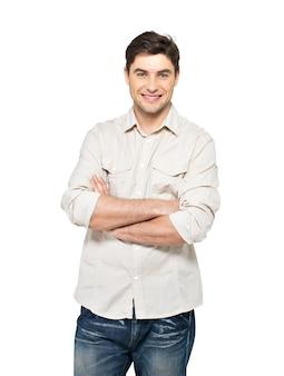 Portret uśmiechnięty szczęśliwy przystojny mężczyzna w przypadkowych - na białym tle na białej ścianie
