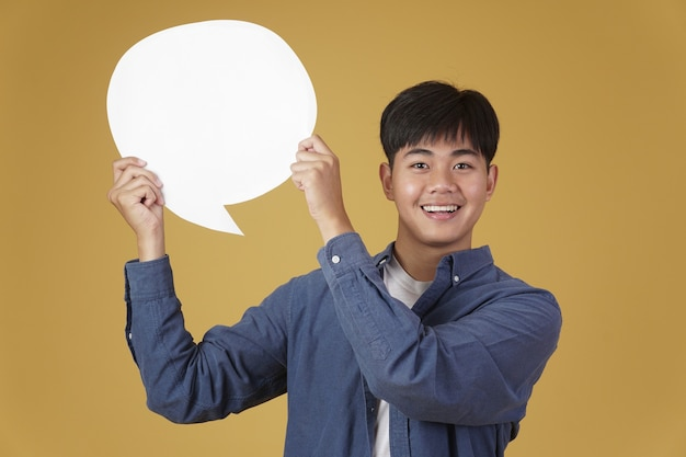Portret uśmiechnięty szczęśliwy wesoły młody azjatycki mężczyzna ubrany niedbale z pustym dymkiem na białym tle